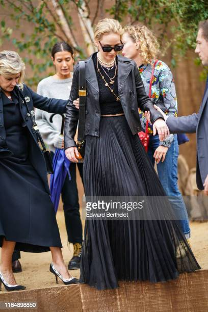 Jennifer Lawrence wears earrings sunglasses necklaces a black lace crop top a black leather jacket a black flowing long pleated skirt a black bag...