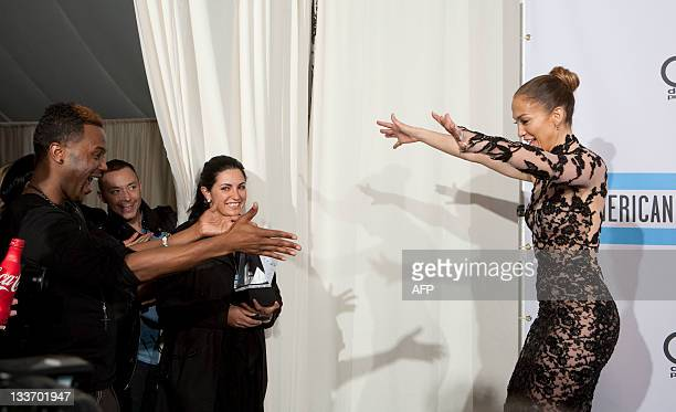 Jennifer Lopez is congratulated after winning Best Latin Music Artist award in the press room during the 2011 American Music Awards at the Nokia...