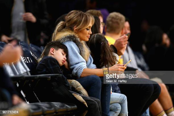 Jennifer Lopez looks at her phone during the second half of a game between the Los Angeles Lakers and the Charlotte Hornets at Staples Center on...