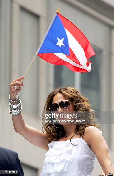 Jennifer Lopez shows her pride as she waves a flag while riding a float up Fifth Ave during the 50th annual Puerto Rican Day Parade