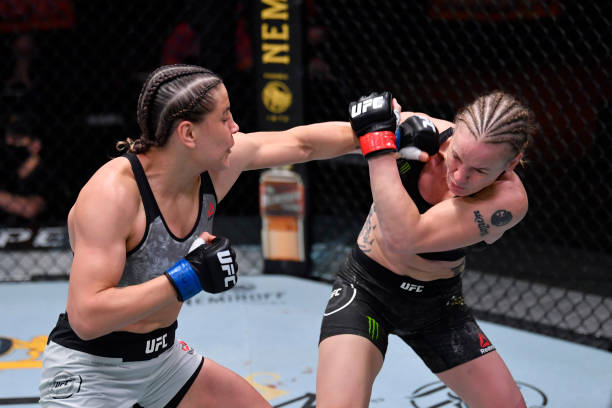Jennifer Maia of Brazil punches Valentina Shevchenko of Kyrgyzstan in their women's flyweight championship bout during the UFC 255 event at UFC APEX...