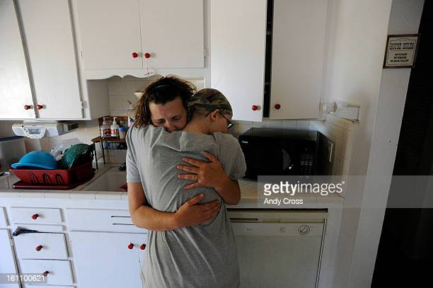 Jennifer Marlowe, front, hugs her mother, Sharon, left, after receiving dire medical news about Sharon's mother Friday afternoon at their house in...