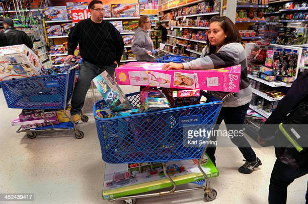 Jennifer Martinez filled a shopping cart with toys at the Toys R Us store on County Line Road in Arapahoe County Thursday night November 28 2013 Many...
