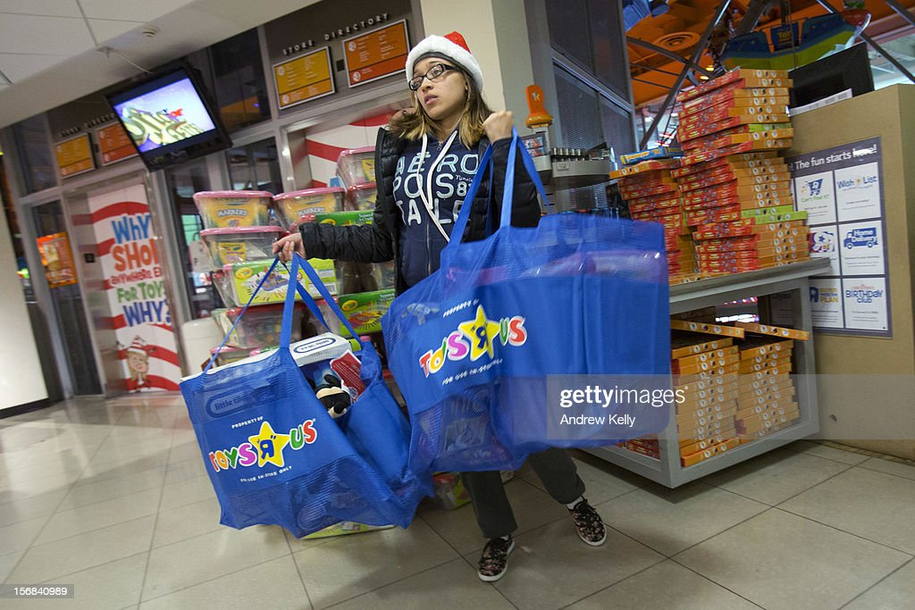 Jennifer Melendez struggles to carry bags of goods at the Black Thursday sale at the Toys 'R' Us store in Times Square November 22, 2012 in New York City.The store got a head start on the traditional Black Friday sales by opening their doors at 8pm on Thanksgiving night.