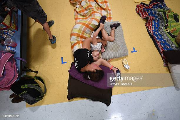 Jennifer Miller and her daughter Jubilee rest laying on the floor of a makeshift shelter at the Timberlin Creek Elementary School in St. Augustine,...
