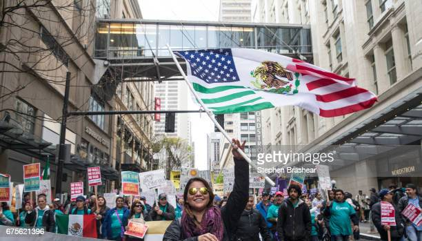 Jennifer Molina waves a flag while walking through downtown during during the Workers and Immigrant Rights March on May 1 2017 in Seattle Washington...
