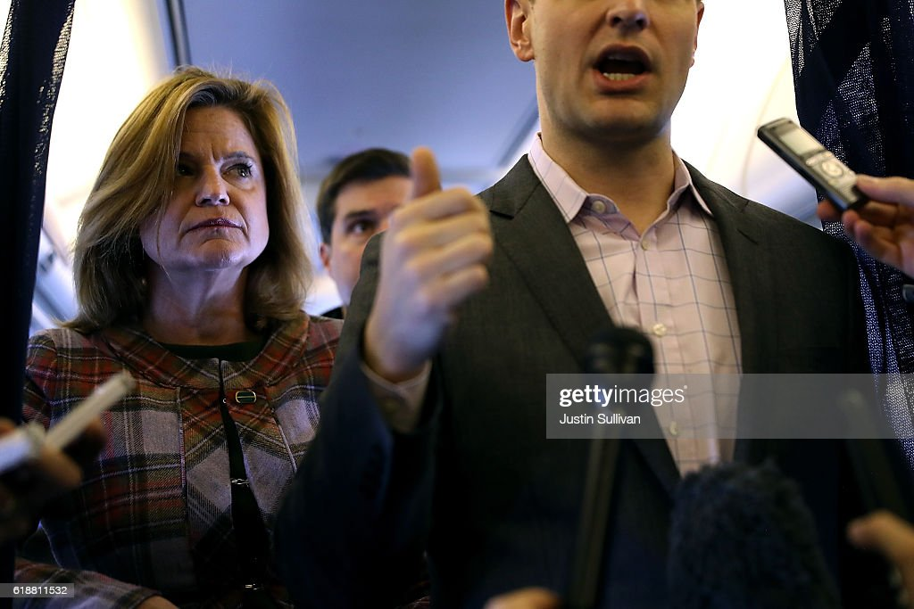 Jennifer Palmieri, communications director for Democratic presidential nominee former Secretary of State Hillary Clinton looks on as campaign manager Robby Mook speaks aboard the campaign plane while traveling to Cedar Rapids, Iowa October 28, 2016. With less than two weeks to go until election day, Hillary Clinton is campaigning in Iowa.