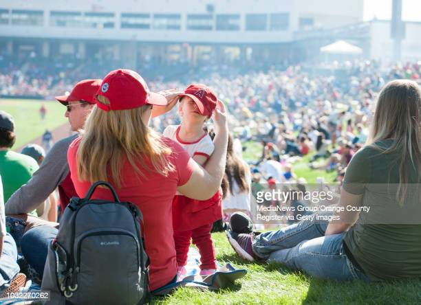 Jennifer Pyenson of Lake Forest helps her daughter Talia with her Angels hat during the Angels' Spring Training homeopener against the Milwaukee...