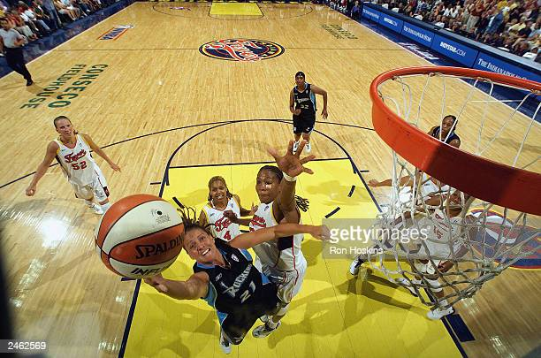 Jennifer Rizzotti of the Cleveland Rockers shoots a layup past Tamika Catchings and Coquese Washington of the Indiana Fever during the game at...