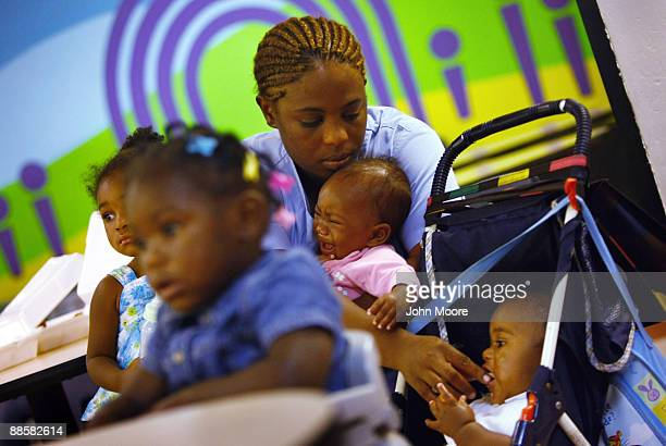 Jennifer Ross, living in a homeless shelter with her five children, holds one child while feeding another on June 18, 2009 in Dallas, Texas. Ross...