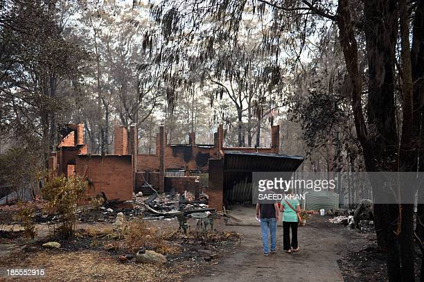 Jennifer Schweinsberg with her son David walks towards her gutted house in Winmalee in the Blue Mountains on October 22 2013 Jennifer visited her...