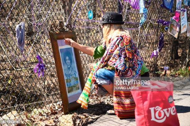 Jennifer Umolac of Minneapolis burns a stick of palo santo next to a photograph of Prince after she placed on the fence next to Paisley Park on the...
