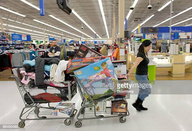 Jennifer Yen pulls to shopping carts full of items at WalMart Supercenter in Denver Colorado US on Friday Nov 27 2009 Shoppers gathered at Best Buy...