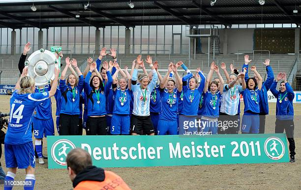 Jennifer Zietz of Potsdam holds up the trophy next to her team mates who celebrate after winning the Women Bundesliga match between Turbine Potsdam...