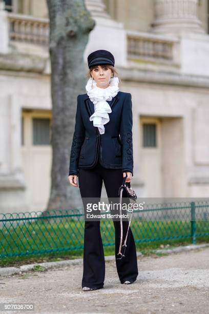 Jenny Cipoletti wears a black hat a white ruffle scarf a blazer jacket flare pants a bag during Paris Fashion Week Womenswear Fall/Winter 2018/2019...
