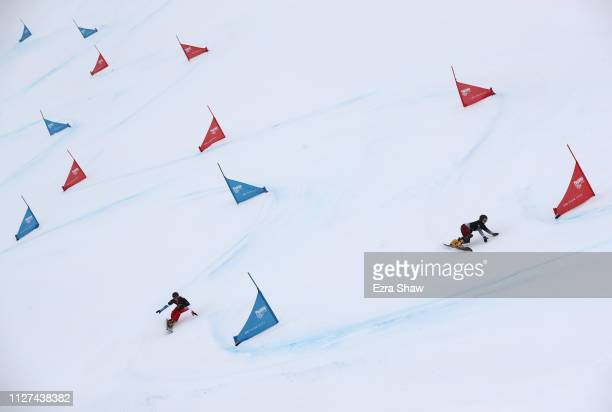 Jenny Ladina of Switzerland races against Milena Bykova of Russia in the small final of the Ladies' Parallel Giant Slalom Finals at the FIS Snowboard...