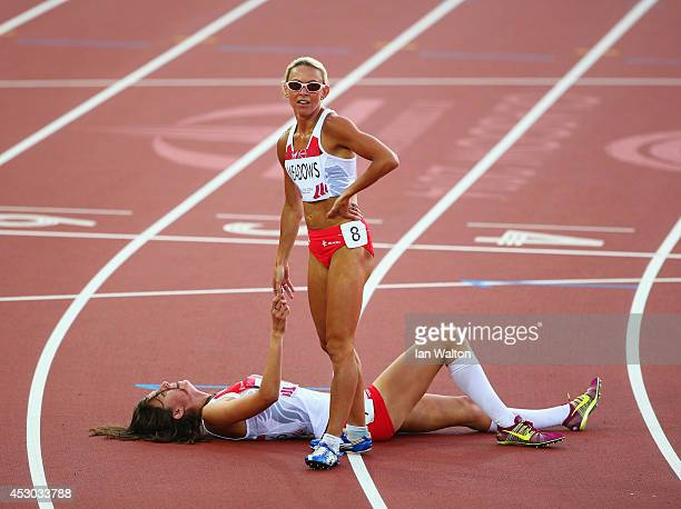 Jenny Meadows of England helps Jessica Judd of England to her feet after the Women's 800 metres final at Hampden Park during day nine of the Glasgow...