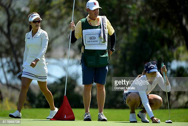 Jenny Shin walks past Lydia Ko of New Zealand as she lines up her putt on the 1st hole during Round Three of the KIA Classic at the Park Hyatt Aviara...