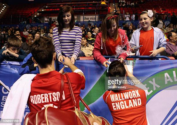 Jenny Wallwork and Nathan Robertson of England sign autographs after winning their round one mixed doubles match in the Yonex All England Badminton...