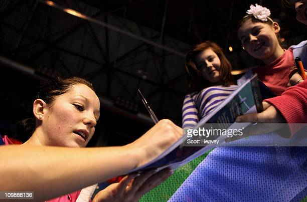 Jenny Wallwork of England signs autographs after her first round defeat in the womens doubles during the Yonex All England Badminton Open...