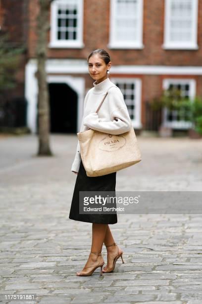 Jenny Walton wears a white turtleneck wool pullover, a Prada large bag, a black skirt, brown heels shoes, pearl earrings, during London Fashion Week...