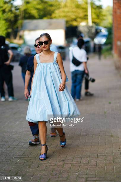 Jenny Walton wears earrings, sunglasses, a strappy light blue puffy dress, lustrous blue ankle-straps sandals , during London Fashion Week September...