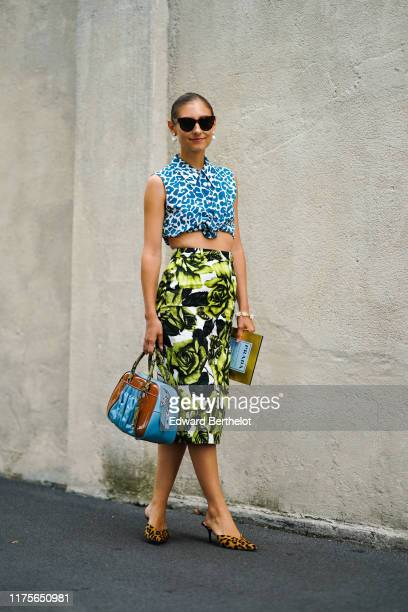 Jenny Walton wears sunglasses a blue and white cropped sleeveless top with printed patterns a green khaki and white floral print skirt a blue and...