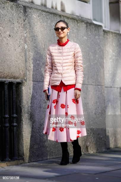 Jenny Walton wears sunglasses a pink puffer jacket a pink flower print skirt black boots during London Fashion Week February 2018 on February 17 2018...