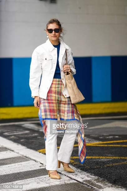 Jenny Walton wears sunglasses, peal earrings, a white denim jacket, a blue top, a colored checked skirt, white pants, pointy checkered shoes, a Prada...