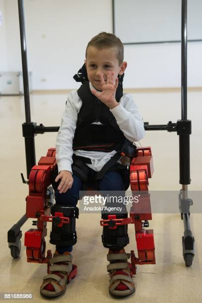 Jens a 5 yearold boy diagnosed with spinal muscular atrophy waves hand as he walks with a new Marsi Bionics exoskeleton that designed for disabled...
