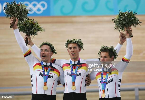 Jens Fiedler, Carsten Bergeman and Rene Wolff of Germany celebrate on the podium with their gold medals after winning the men's track cycling team...