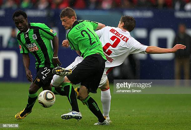 Jens Hegeler of Augsburg battles for the ball with Sandro Kaiser and Eke Uzoma of Muenchen during the Second Bundesliga match between FC Augsburg and...