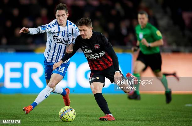 Jens Jakob Thomasen of OB Odense and Mikkel Duelund of FC Midtjylland compete for the ball during the Danish Alka Superliga match between FC...