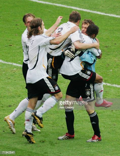 Jens Lehmann of Germany is mobbed by his team mates following his decisive save of Esteban Cambiasso's penalty to give his team victory in a penalty...