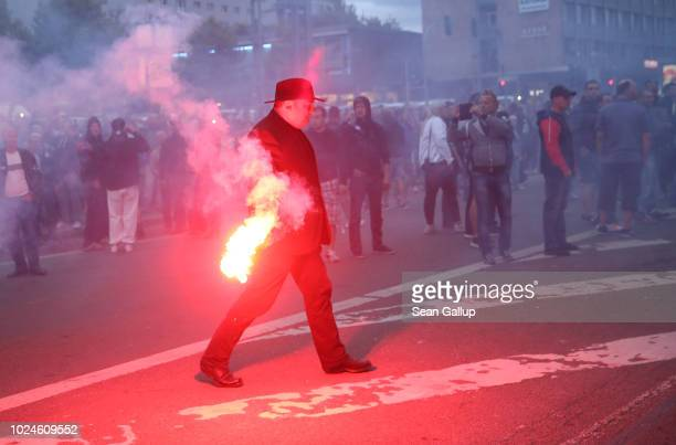 Jens Lorek a lawyer for the rightwing Pegida movement carries away flares thrown during a confrontation between left and rightwing protesters the day...