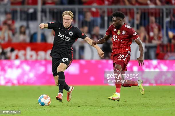 Jens Petter Hauge of Eintracht Frankfurt and Alphonso Davies of Bayern Muenchen battle for the ball during the Bundesliga match between FC Bayern...