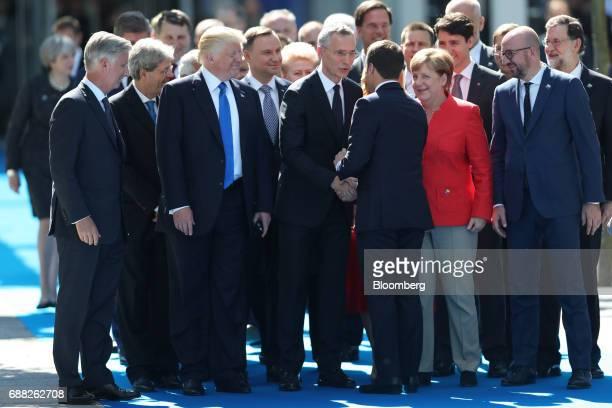 Jens Stoltenberg secretary general of the North Atlantic Treaty Organization center shakes hands with Emmanuel Macron France's president as world...