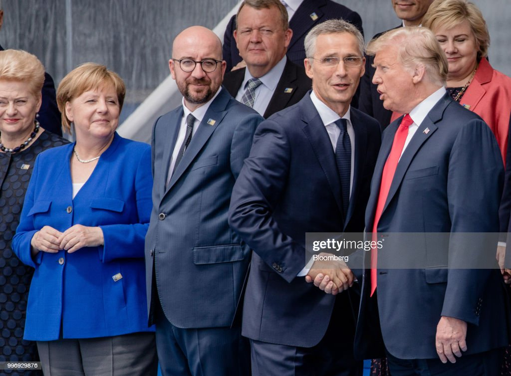 Jens Stoltenberg, secretary general of the North Atlantic Treaty Organization (NATO), second right, shakes hands with U.S. President Donald Trump as Angela Merkel, Germany's chancellor, second left, Charles Michel, Belgium's prime minister, second left, and other world leaders gather for a family photograph during the NATO summit, at the military and political alliance's headquarters in Brussels, Belgium, on Wednesday, July 11, 2018. President Donald Trump opened up another front in his tussle with allies on his arrival at NATOs annual summit, targeting Germany over its support for the Nord Stream 2 gas pipeline from Russia. Photographer: Marlene Awaad/Bloomberg via Getty Images