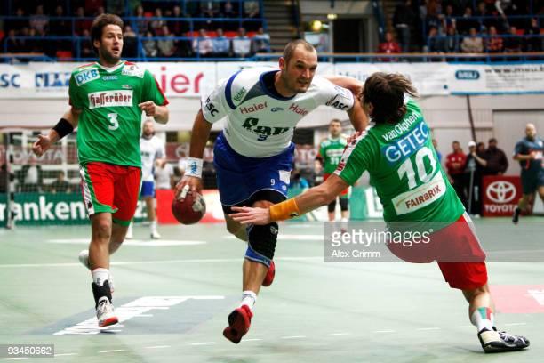 Jens Tiedtke of Grosswallstadt is challenged by Fabian van Olphen and Bennet Wiegert of Magdeburg during the Toyota Handball Bundesliga match between...