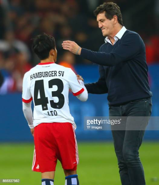 Jens Todt of Hamburg shakes hands with Tatsuya Ito of Hamburg during the Bundesliga match between Bayer 04 Leverkusen and Hamburger SV at BayArena on...