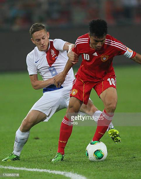 Jens Toornstra of Netherlands fights for a ball against Zheng Zhi of China during the friendly match at Beijing Workers' Stadium on June 11 2013 in...