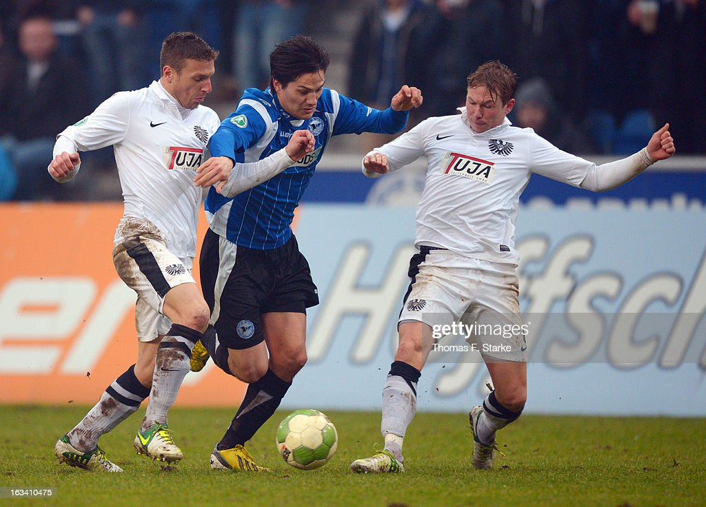 Jens Truckenbrod (L) and Kevin Schoeneberg (R) of Muenster tackle Tim Jerat of Bielefeld during the Third League match between Arminia Bielefeld and Preussen Muenster at Schueco Arena on March 9, 2013 in Bielefeld, Germany.