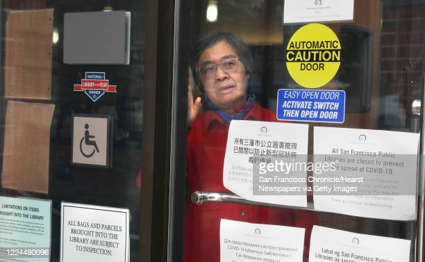 Jensa Woo has been a librarian for the past 40 years and looks through the window at the SF Public Library Merced Branch which is presently closed as...
