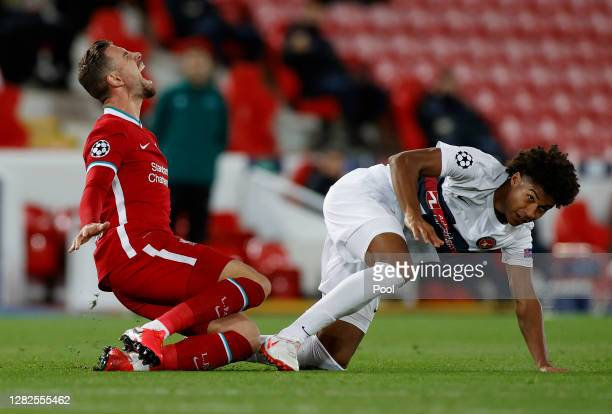 JensLys Cajuste of FC Midtjylland tackles Jordan Henderson of Liverpool during the UEFA Champions League Group D stage match between Liverpool FC and...