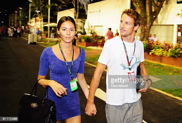 Jenson Button of Great Britain and Brawn GP and his girlfriend Jessica Michibata walk in the paddock during previews to the Singapore Formula One...