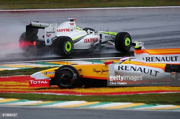 Jenson Button of Great Britain and Brawn GP drives by as Romain Grosjean of France and Renault spins in the rain affected final practice session...
