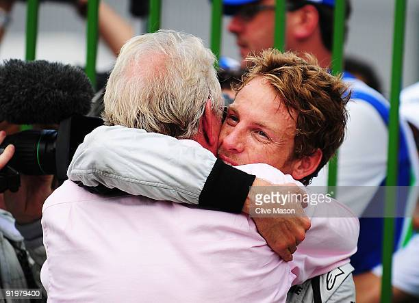 Jenson Button of Great Britain and Brawn GP is congratulated by his father John Button after clinching the F1 World Drivers Championship during the...