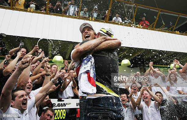 Jenson Button of Great Britain and Brawn GP is congratulated by team mate Rubens Barrichello of Brazil and Brawn GP as he celebrates in the pitlane...