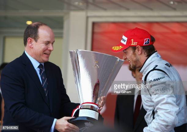Jenson Button of Great Britain and Brawn GP is presented with the winners trophy by Prince Albert II of Monaco after his victory in the Monaco...