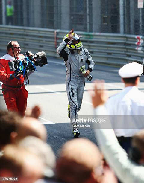 Jenson Button of Great Britain and Brawn GP runs back to the podium after winning the Monaco Formula One Grand Prix at the Monte Carlo Circuit on May...